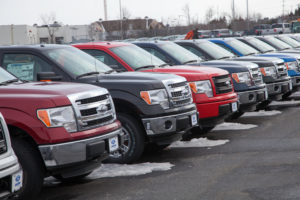 Dartmouth, Nova Scotia, Canada - February 23, 2014: New Ford F-150 vehicles in a row at a car dealership. Vehices display informational signs on passenger window. Other vehicles in background.