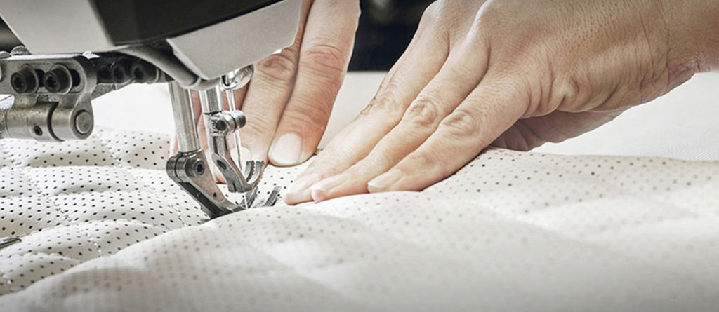 Zoomed in view of someone's hands using a sewing machine stitching together white leather seats