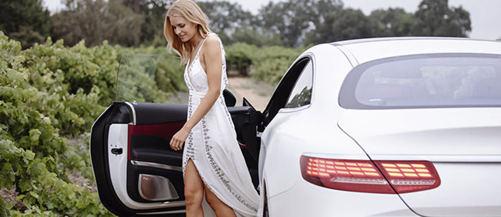 Woman in a white dress getting out of the drivers door of a white S-class Coupe