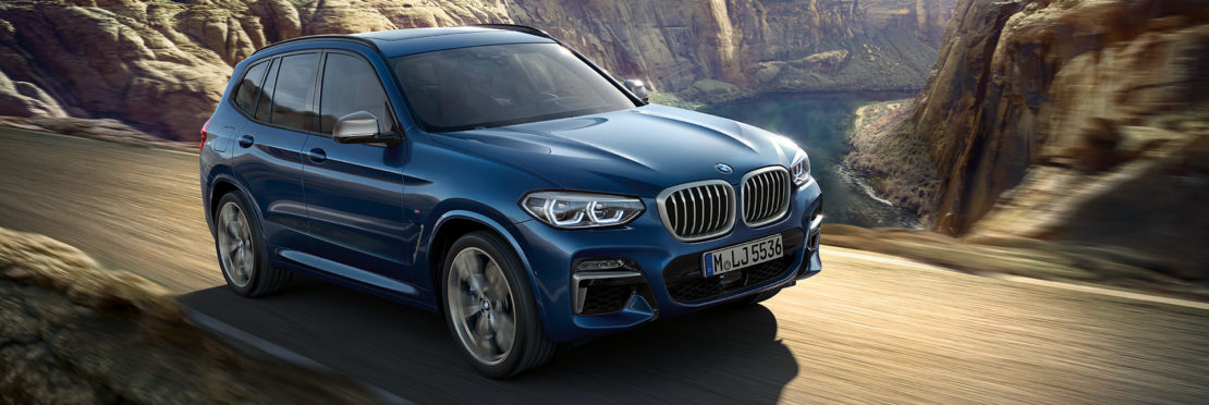BMW X3 in blue driving on a road with a backdrop of a canyon