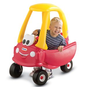 Red Little Tikes Cozy Coupe with an eyes and mouth on its front with a blonde kid inside of it