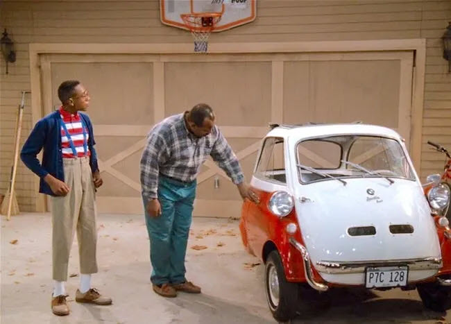 Big Daddy Urkel and his son, Steve, looking at a red and white BMW Isetta on the show Family Matters
