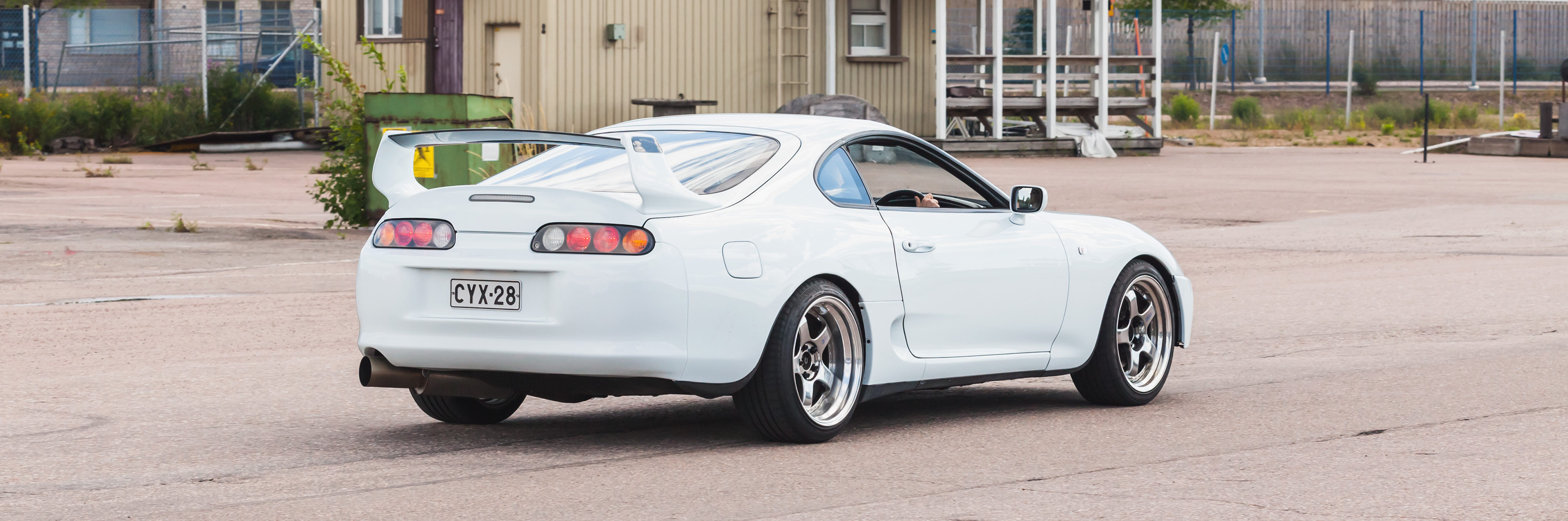 White Toyota Supra A80 goes down the street in European town