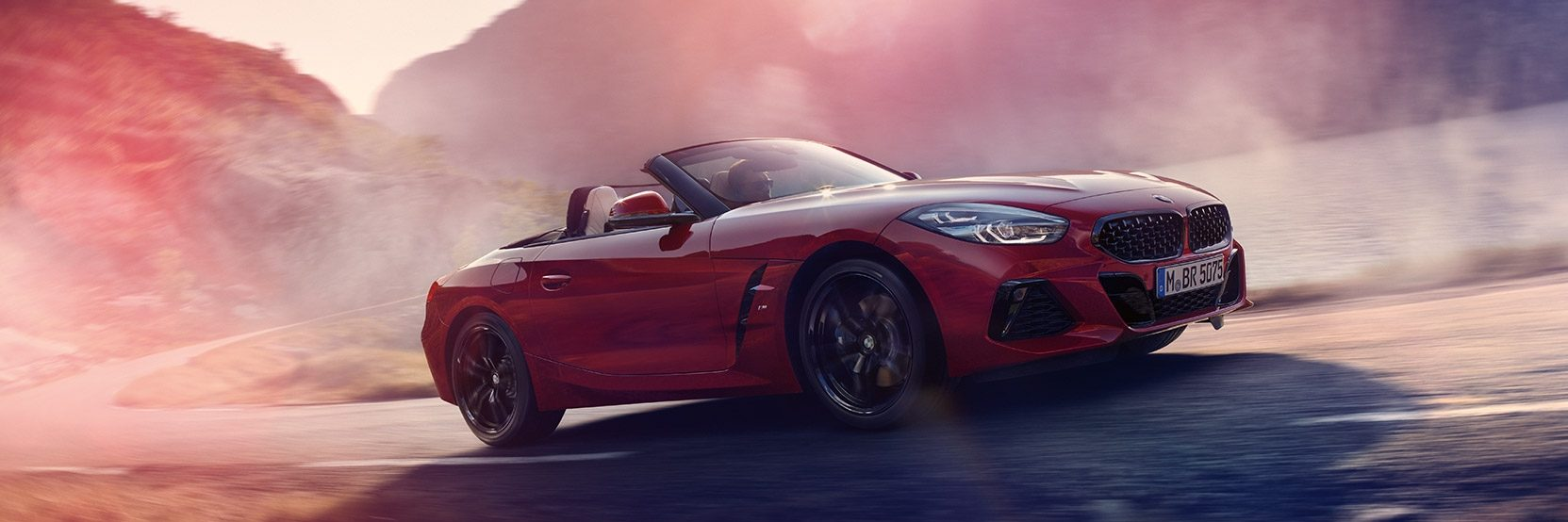 Red BMW Z4 in motion by body of water, sun glare in shot