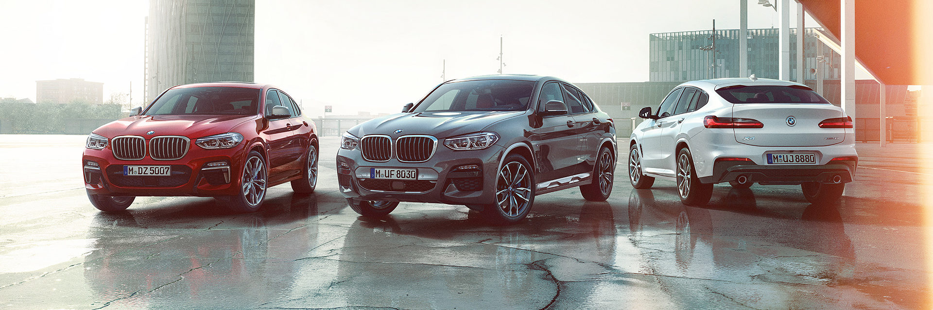 Lineup of three BMW X4s in red, grey and silver, parked staggered in city