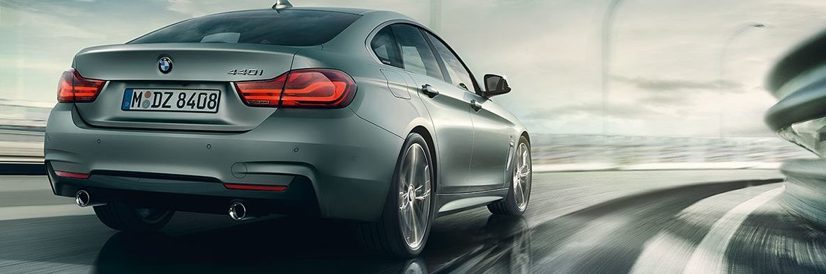 Rear shot of BMW 4 Series Gran Coupe taking a high speed corner, grey skies