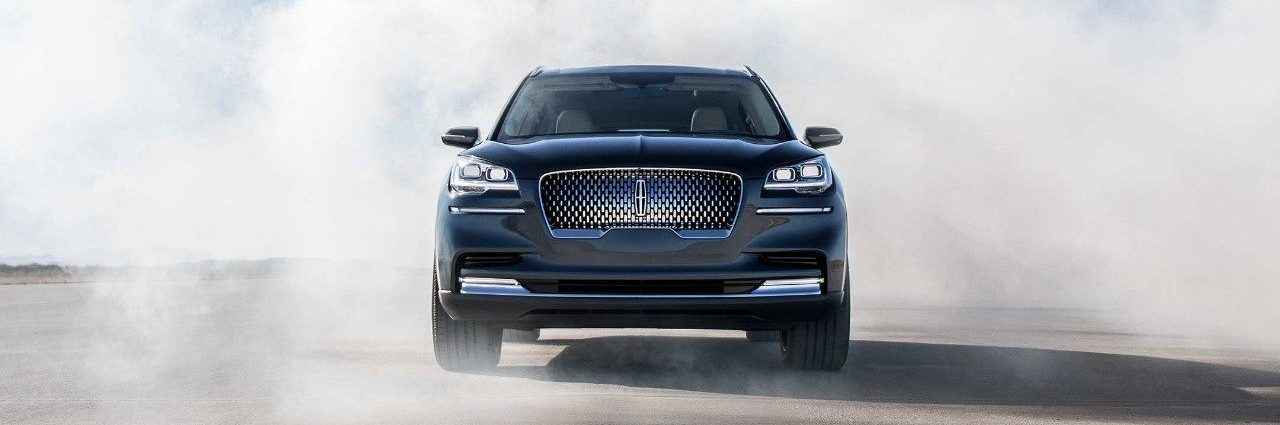 Front shot of Lincoln Aviator driving through cloudy haze, mimicking clouds