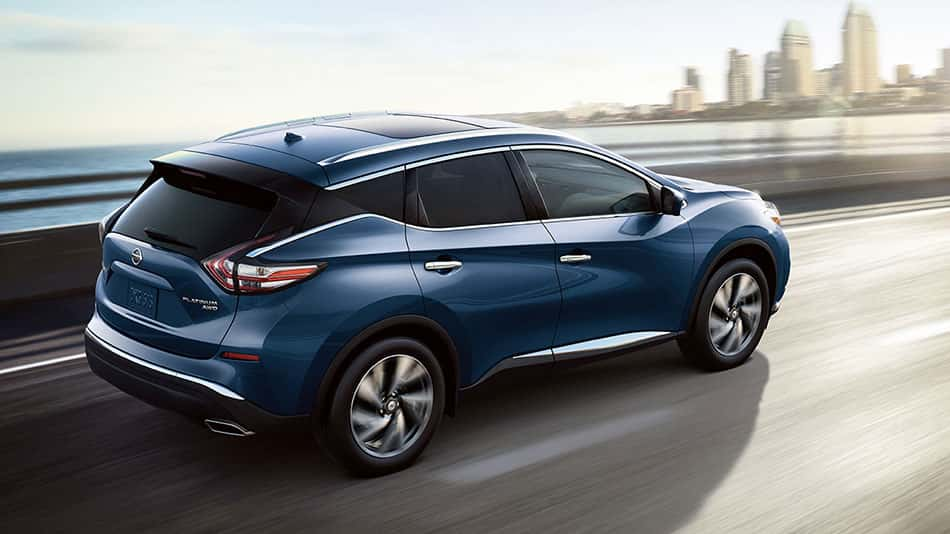 A blue 2018 Nissan Murano, speeding across a bridge toward the big city