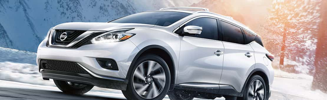 A platinum 2018 Nissan Murano, driving through a winter wonderland