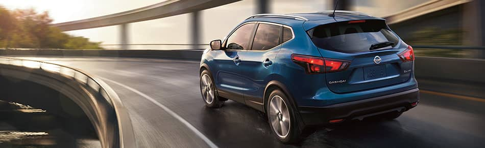2019 Nissan Qashqai in blue driving into the sunset on a traffic circle bridge
