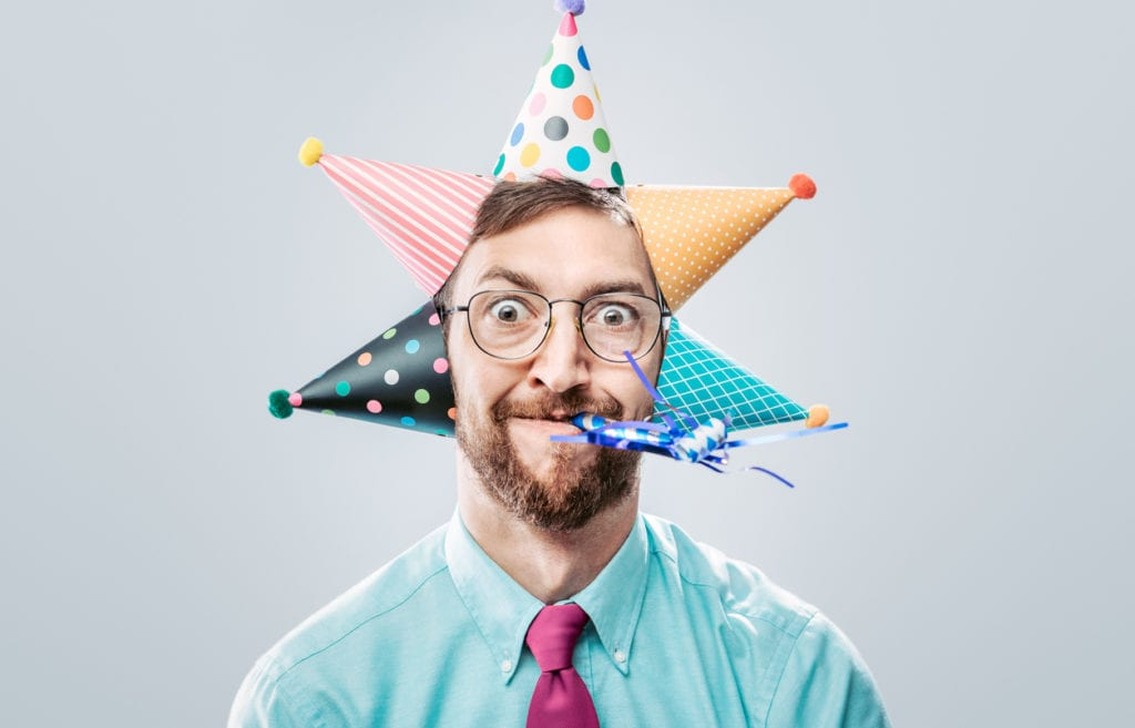 A portrait of a man wearing business office attire sporting many birthday hats and party horn blower. He has a crazy look on his face.