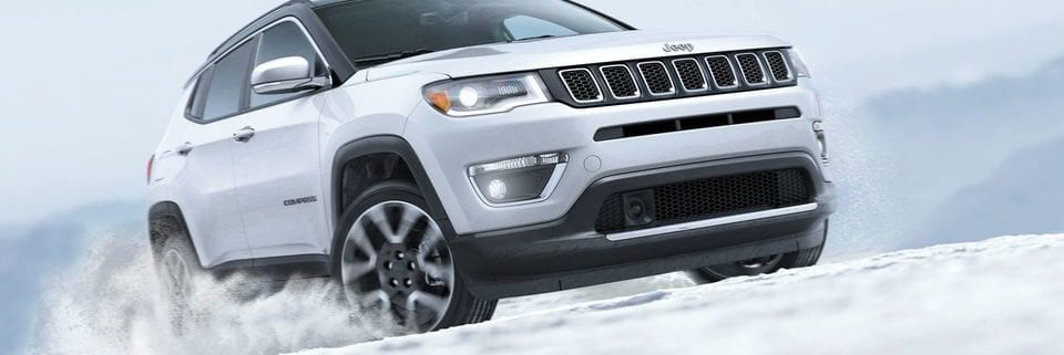 white jeep compass driving on snowy road