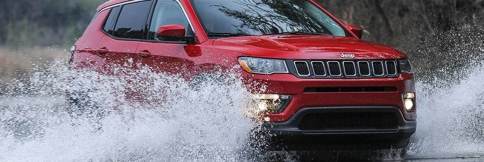 Red jeep compass driving through water in forest