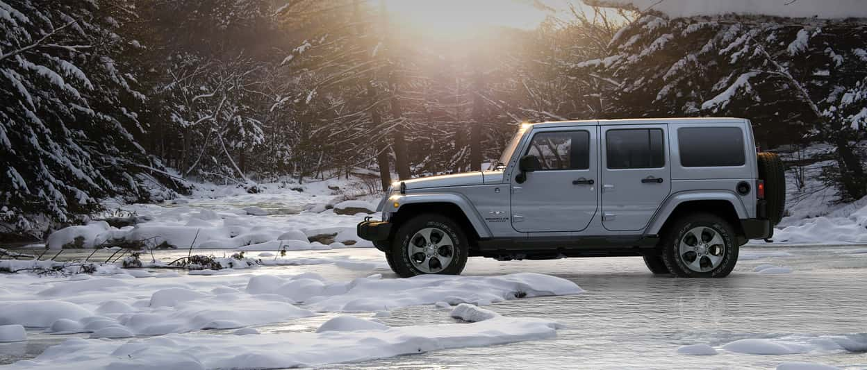 A white 2018 Jeep Wrangler forges its own trail across an icy stream
