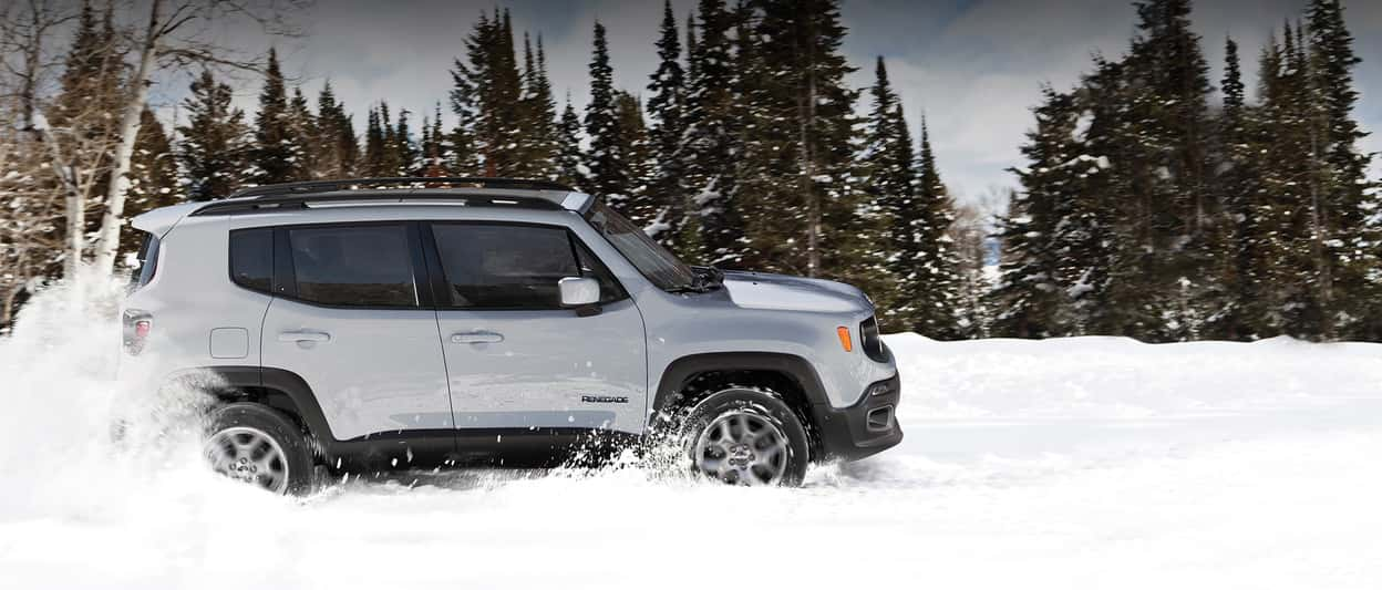 A white 2018 Jeep Renegade drives through snowy terrain