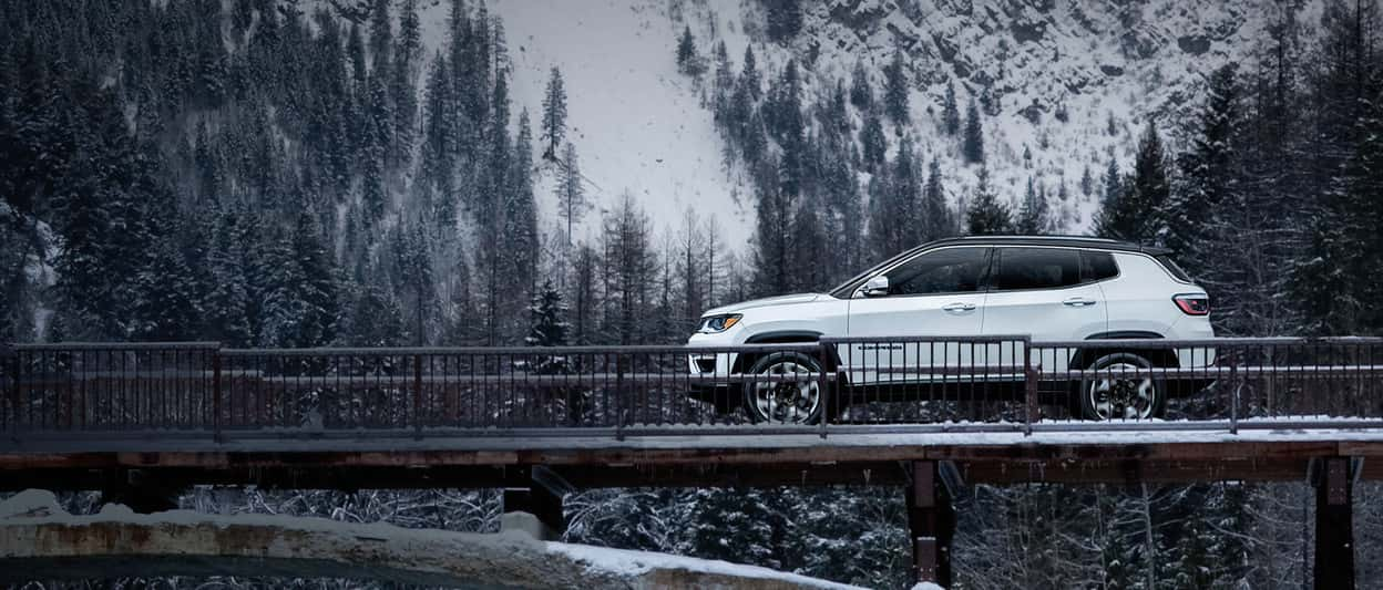 A white 2019 Jeep Compass parked on a mountain bridge in the dead of winter