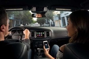 A driver and passenger interact with the Uconnect console on the front dash of a Dodge Charger