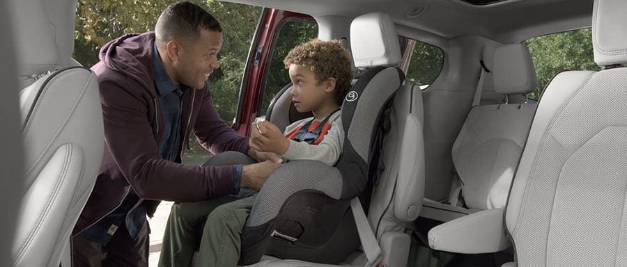 Man seating a child in 2018 Chrysler Pacifica safety seating