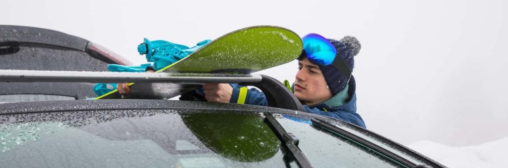 A man loads a snowboard onto his roof rack