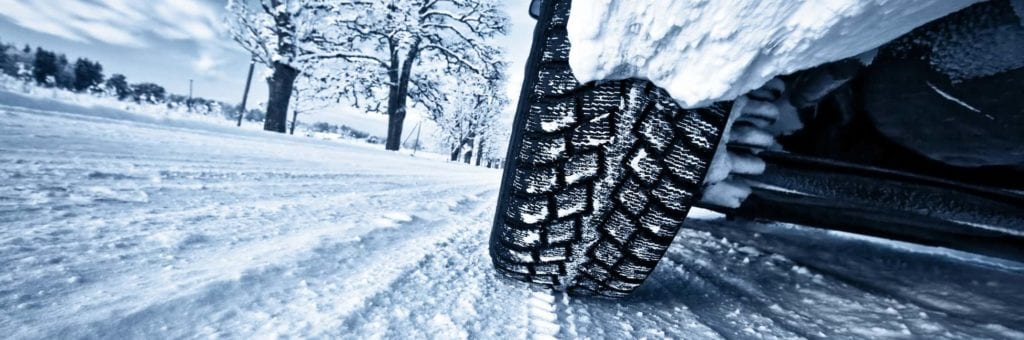 A winter tire grips the snowy road