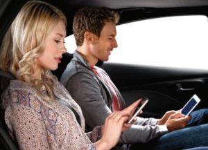 Passengers enjoy the Uconnect features of a Chrysler vehicle from the backseat, looking at the smartphones