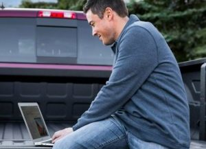 A man uses the Uconnect Wi-Fi hotspot feature to do some work on his laptop from the bed of his truck