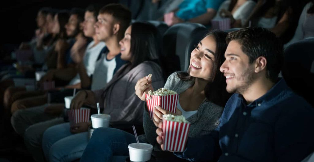 Beautiful latin couple that I want to live vicariously through enjoys each other's company while watching a movie and eating popcorn