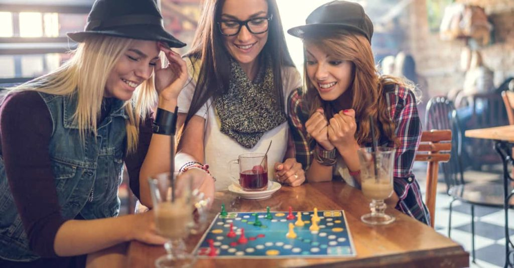 A bunch of trendy, hip ladies having fun at an equally trendy, hip board game cafe