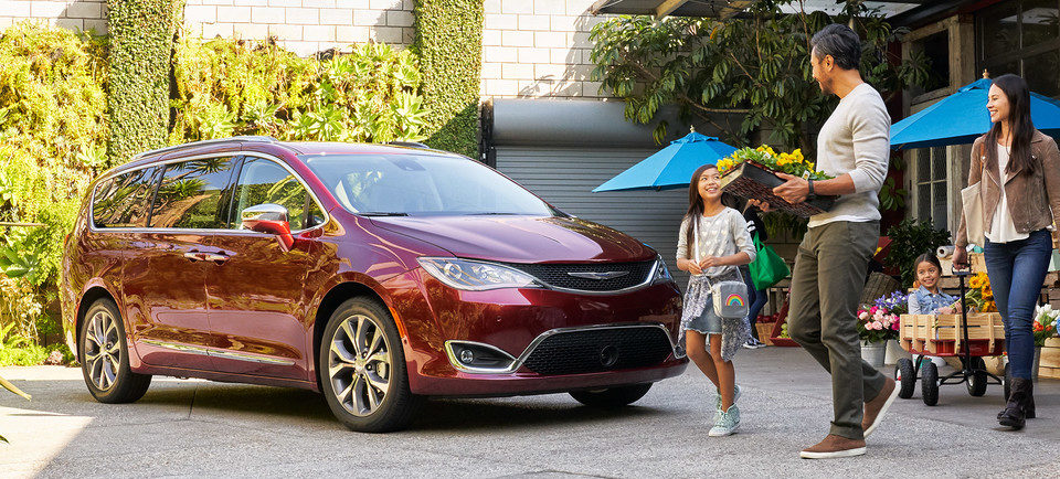 young family of asian-american descent carrying flowers and other potted plants to their cherry red 2019 chrysler pacifica