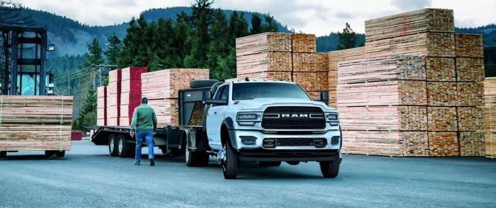 A new 2019 Ram Chassis Cab with utility upfit drives through a construction site.
