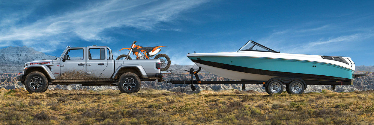 2020 Jeep Gladiator towing a boat with a dirtbike in the box
