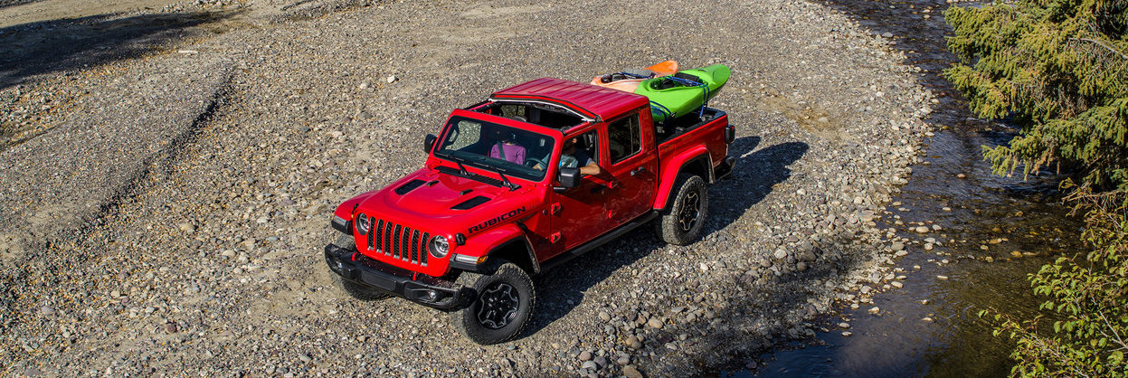2020 Jeep Gladiator with kayaks in the box parked on a gravel bank of a stream