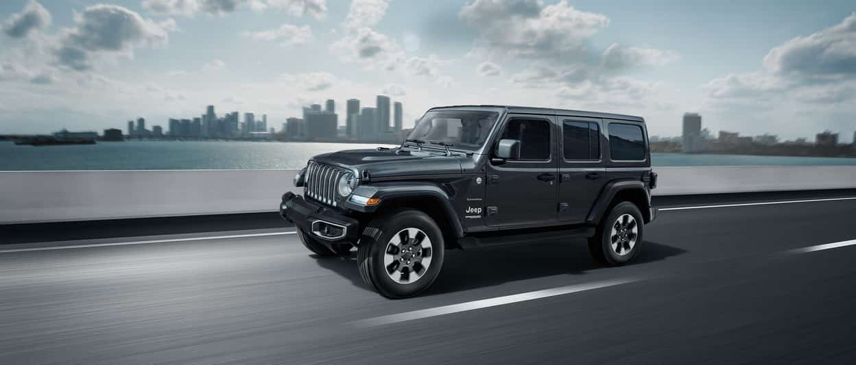 2019 Jeep Wrangler Sahara in grey driving along a highway with a city backdrop in the background
