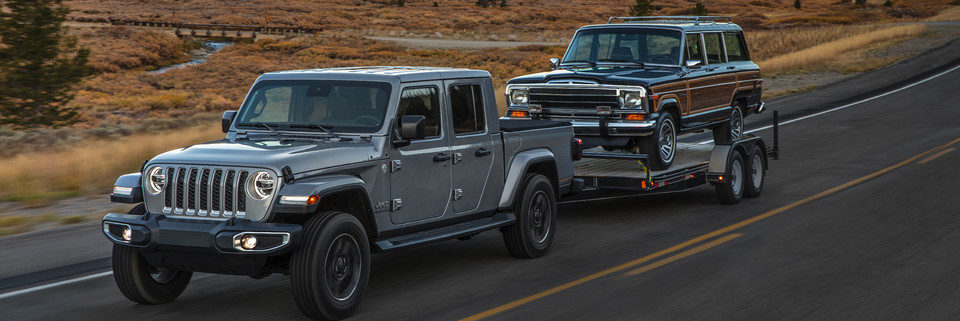 Jeep Gladiator towing a trailer with an old Jeep on it