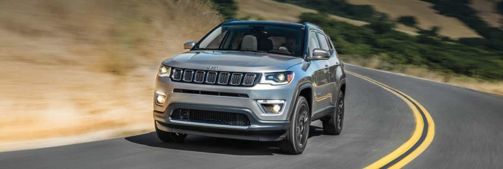 2019 Jeep Compass in grey driving along a curved highway