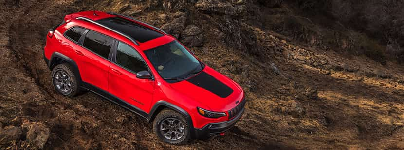 Jeep Cherokee in red driving through a downhill dirt road