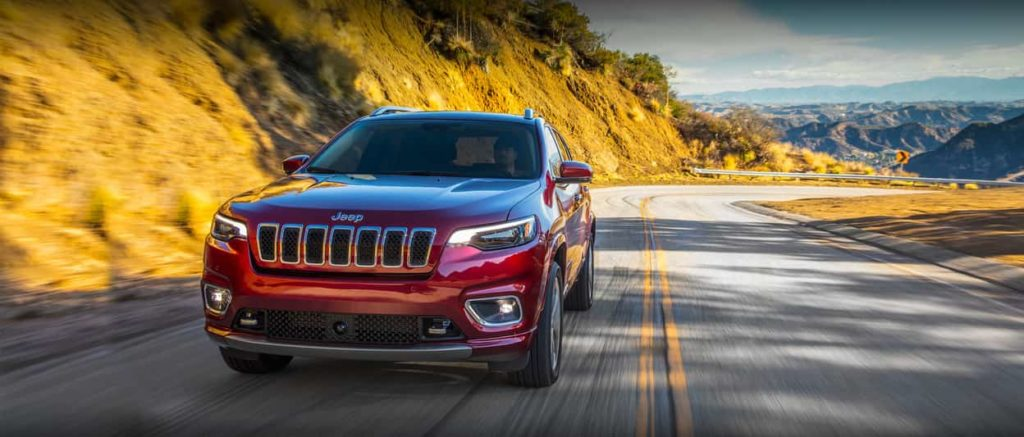 Jeep Cherokee in dark red driving on an uphill highway