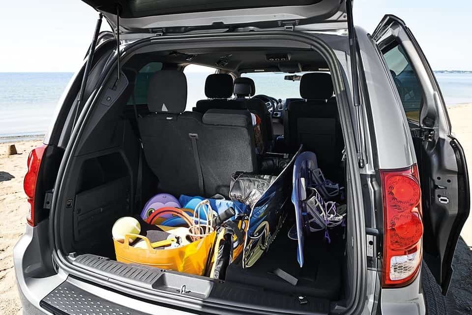 Picnic items loaded inside the storage space for the Grand Caravan on a beach