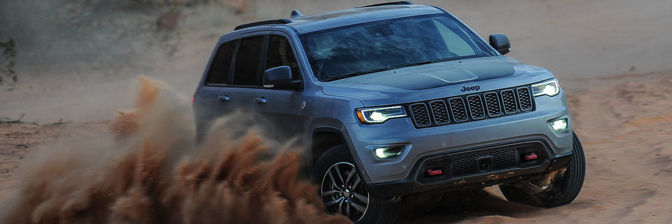 2019 Jeep Grand Cherokee driving in sand and kicking it up