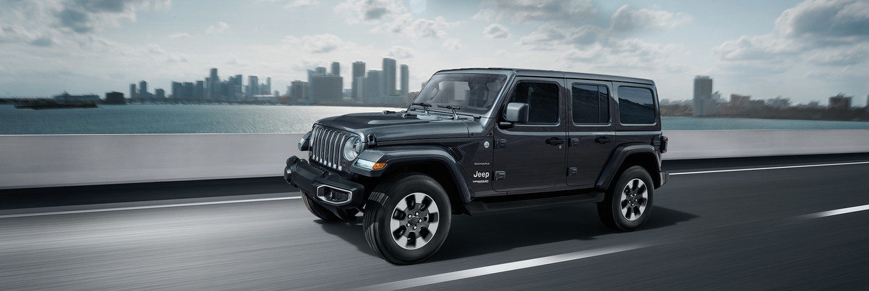 2019 Jeep Wrangler Sahara driving on a road by water by a city