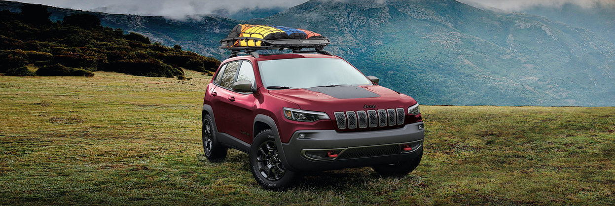 2020 Jeep Cherokee on the grass by a mountain