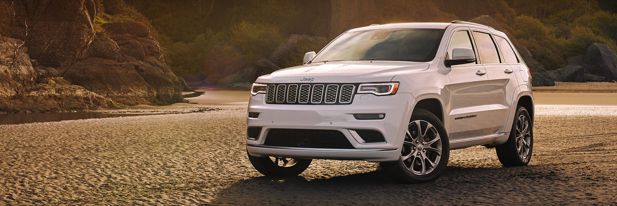 2020 Jeep Grand Cherokee parked on sand by some rocks