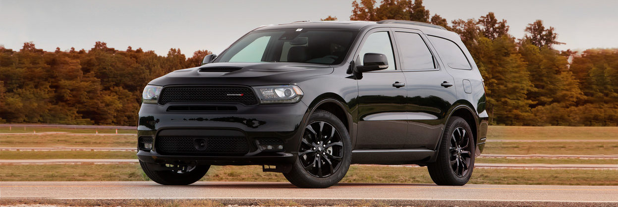 2019 Dodge Durango parked on a paved road in front of a bunch of trees