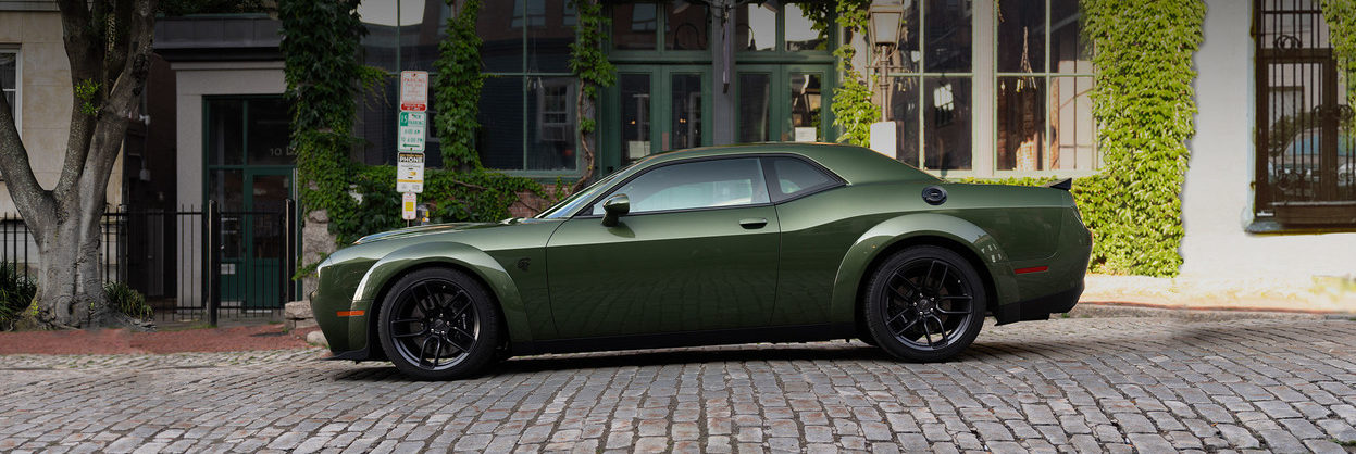 Side of a 2019 Dodge Challenger SRT parked on a road next to a building covered in greenery