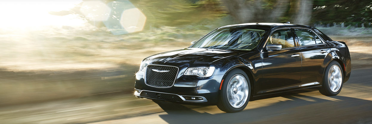 2019 Chrysler 300 driving down a country road past a blurry background of a tree and field