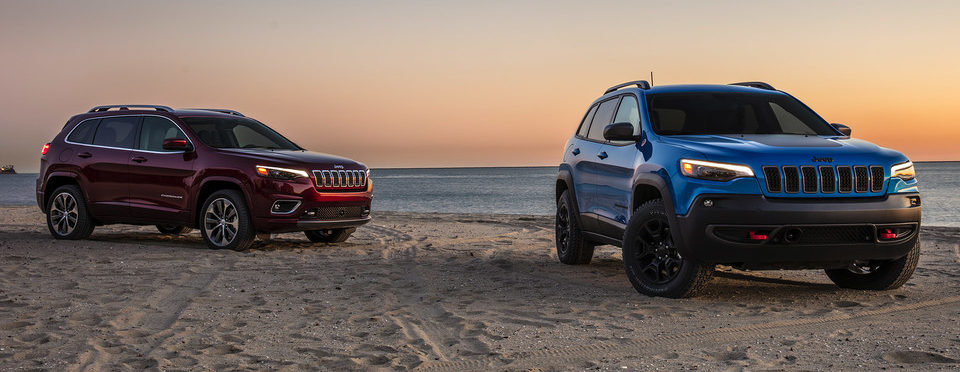 Two 2020 Jeep Cherokees parked on sandy beach, sun is on the horizon casting a somber pink sky
