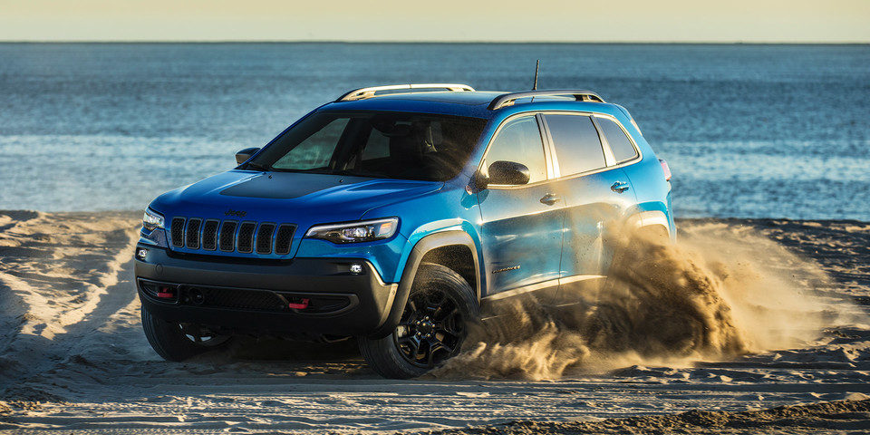 2020 Jeep Cherokee shown in blue drifting on beach, kicking up sand