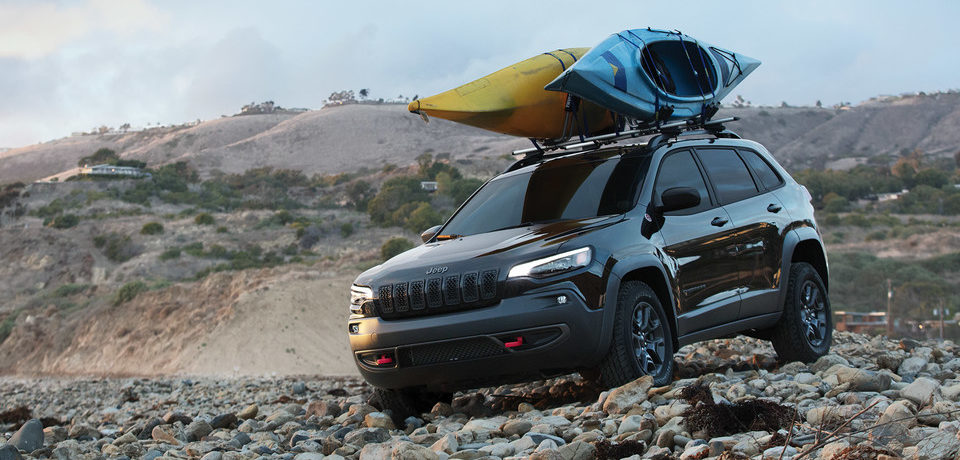 2020 jeep cherokee driving on a beach with kayaks on top