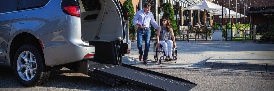 2020 Chrysler Pacifica with a wheelchair ramp on the back and a guy and woman in a wheelchair approaching