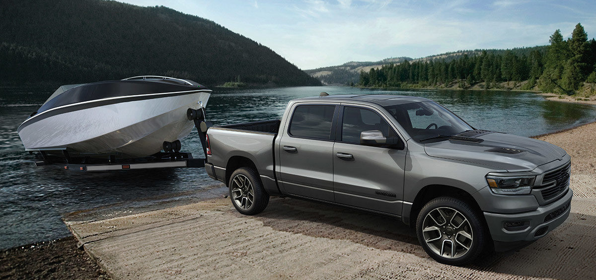 ram 1500 with a boat in tow, backing it into the water